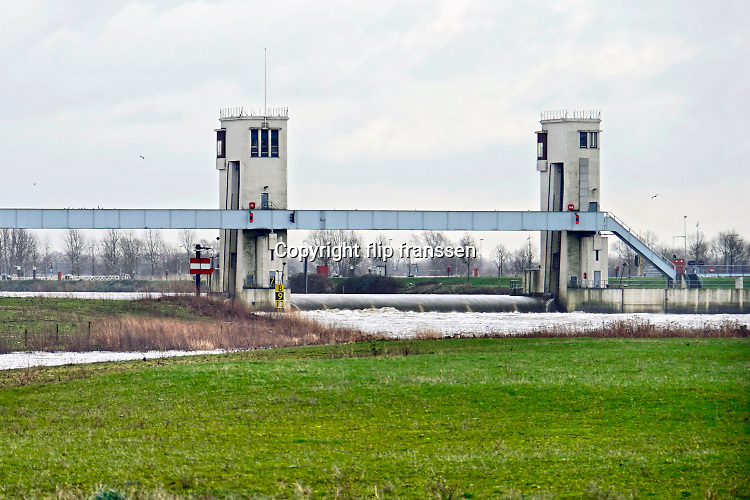 Nederland, Lith, 26-2-2020 De sluis en stuw bij Lith in de Maas. Het water stroomt vrij door de stuw omdat het hoog staat. De waterstand in de Maas wordt in Nederland door de mens gereguleerd middels stuwen. Als er teveel aanvoer is staan deze open en kan het sneller wegstromen naar zee. Bij weinig aanvoer wordt het per vak op hoogte gehouden. Langs de Maas tussen Grave en Lith moeten nog belangrijke aanpassingen gedaan worden door Rijkswaterstaat om de rivier klaar te maken voor de toekomst . Foto: Flip Franssen