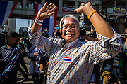 """15 JANUARY 2014 - BANGKOK, THAILAND:  SUTHEP THAUGSUBAN, former Deputy Prime Minister of Thailand and leader of the Shutdown Bangkok anti-government protests, walks through the protest site in the Asoke intersection. Tens of thousands of Thai anti-government protestors continued to block the streets of Bangkok Wednesday to shut down the Thai capitol. The protest, """"Shutdown Bangkok,"""" is expected to last at least a week. Shutdown Bangkok is organized by People's Democratic Reform Committee (PRDC). It's a continuation of protests that started in early November. There have been shootings almost every night at different protests sites around Bangkok. The malls in Bangkok are still open but many other businesses are closed and mass transit is swamped with both protestors and people who had to use mass transit because the roads were blocked.   PHOTO BY JACK KURTZ"""
