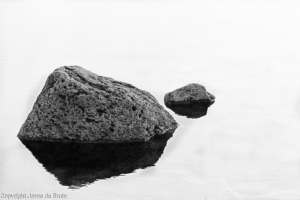 Two rocks in the misty water of a highland pool on the western cliffs of Iceland.