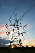 Two forms of Energy - setting sun shining through electricity pylons which blot the landscape, at sunset in United Kingdom