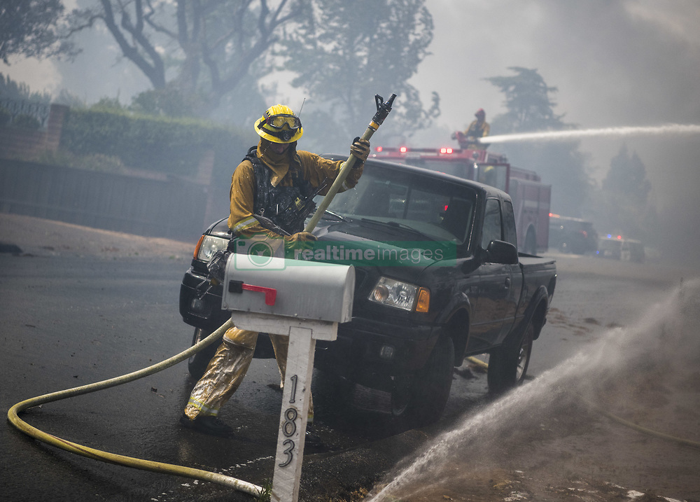 July 6, 2018 - Alpine, San Diego County, USA - Firefighters spray water on a structure burned due to the West Fire in Alpine, CA. ..The West Fire burns in Alpine, CA San Diego County, USA Friday July 6th, 2018. By afternoon the fire had burned 400 acres, destroyed multiple homes, and was 0% contained. (Credit Image: © Stuart Palley via ZUMA Wire)