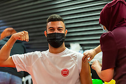 """© Licensed to London News Pictures. 27/06/2021. WATFORD, UK. Tersion Soares (aged 20) receives a first dose of the Pfizer vaccine at a pop-up mass vaccination clinic at Watford FC's Vicarage Road Stadium as part of the """"Grab a jab"""" campaign. The NHS is also promoting a number of walk-in clinics this weekend across the capital to try to increase the number of over 18s receiving a jab as cases of the Delta variant are reported to be on the rise..  Photo credit: Stephen Chung/LNP"""