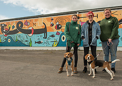 Edinburgh Dog and Cat Home 'unveiled' a colourful 80-foot mural along the Seafield Promenade this morning. The large-scale artwork occupies a wall previously covered in graffiti along the Seafield shoreline. Designed and painted by local artists, Studio N_Name, the mural will embodies the colourful people, heritage and environment of the local community. This project was made possible through a partnership with Edinburgh Shoreline Project, which chose to support the mural as part of their mission to celebrate the city's 27km of coastline. Pictured: Katie Guthrie, one of the artists from Studio N_Name, with Dog and Cat Home staff, and dogs<br /> © Jon Davey/ EEm