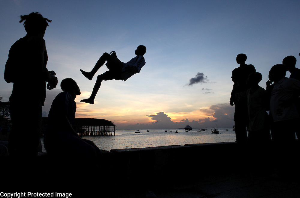 Boys take turns jumping over the harbor wall into the water below in Stone Town in Zanzibar, Tanzania.