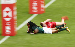 South Africa's Cecil Afrika slides in to score a try during day one of the HSBC London Sevens at Twickenham Stadium, London.