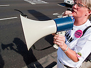 05 JUNE 2009 -- PHOENIX, AZ: Liz Hourican (CQ) from Code Pink, uses a bullhorn to lead a chant in front of Sen John McCain's office in Phoenix. About 25 protestors opposed to the US led wars in Iraq and Afghanistan to visited the Phoenix office of Sen John McCain Friday morning to ask the Senator to vote against confirming General Stanley McChrystal (CQ) as commander of US forces in Afghanistan. The protestors cited McChrystal's alleged involvement of the true circumstances behind the death of former Arizona Cardinal Pat Tillman in Afghanistan and torture of detainees in Iraq. Some of the protestors wore tee shirts with Tillman's name and number 40 on them to show support for the Tillman family, which is also opposed to McChrystal's confirmation.     Photo by Jack Kurtz
