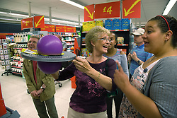 Day Service Officer and Care Assistant looking at a wobble exercise board whilst out shopping with a group of service users with learning disabilities,