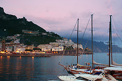 Sunset, sailboat, Amalfi Harbor. Stretching about 30 miles or 50km along the southern side of the Sorrentine Peninsula, most famous for the town of Sorrento, the Amalfi Coast (Costiera Amalfitana) is one of Europe's most breathtaking. Cliffs terraced with scented lemon groves sheer down into sparkling seas; whitewashed and pastel colored villas cling precariously to unforgiving slopes while sea and sky merge in one vast blue horizon.