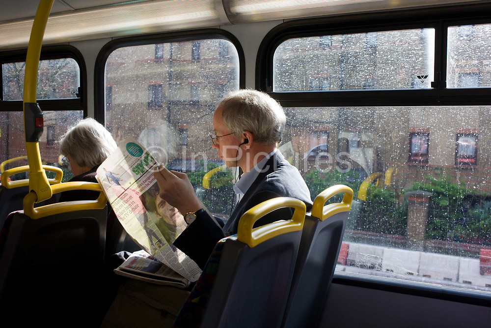 Listening to an mp3 device, a man reads the Sports section of his newspaper on the top deck of a London bus. Listening to an mp3 device, a man reads the Sports section of his newspaper on the top deck of a London bus. Seated by the window of this double-decker, the man has wires from his music device protruding from his ears, listening perhaps to his favourite band or live radio as his commuting journey stops and starts in inner-city traffic. The word Sport can be seen at the top of this newspaper section and we have the idea that football is the subject that he is reading about. Another passenger sits in the row in front and she too appears to be reading, or sleeping. Affordable flats are in the distance outside.