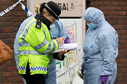 © Licensed to London News Pictures. 19/09/2013. London, UK. A police officer talks to forensic workers at the scene of a fatal shooting on Coppock Close in Battersea London today (19/09/2013). Taking place at around 8pm last night a 19 year old male was pronounced dead at around 9pm. Photo credit: Matt Cetti-Roberts/LNP