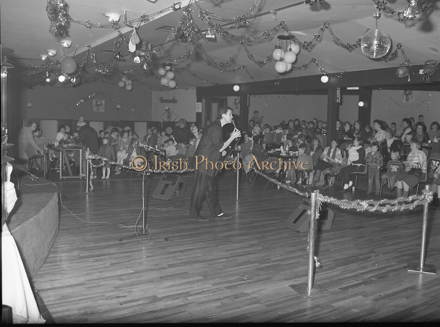 Christmas Party With Johnny Logan..1986..16.12.1986..12.16.1986..16th December 1986..At the 'Embankment',Tallaght, a charity Christmas Party was held for deprived children of the area. The main attraction was the singer and entertainer Johnny Logan,who with his band,entertained the children. Santa Claus took time off from his busy schedule to give a present to all the boys and girls. A great time was had by all..Picture shows Johnny Logan singing to the children and their parents at the party in the Embankment, Tallaght,Co Dublin.