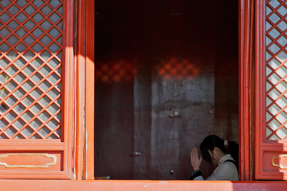 Beijing China, Beijing, China Temple, A woman prays to a statue inside one of Yong He Gong's smaller rooms March 7, 2007.  This Tibetan Temple is known to tourists as Lama Temple and it's located in Dongcheng District Beijing, China. This is the largest Temple of its kind outside of Tibet.  In 1723 the structure was turned into a Temple after the resident became the third Qing Emperor.
