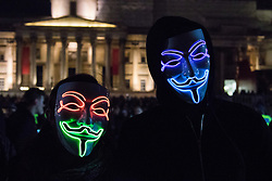 London, November 5th 2016. Anti-capitalists and anarchists participate in the Million Mask March, an annual event that happens on November 5th each year in cities across the world, as part of a protest against the establishment. Many of the protesters wear Guy Fawkes masks, often associated with the internet activism group Anonymous. PICTURED: Two protesters in Trafalgar Square pose with their illuminated masks.