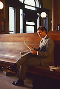 Businessman in a suit reads a financial newspaper in a train station