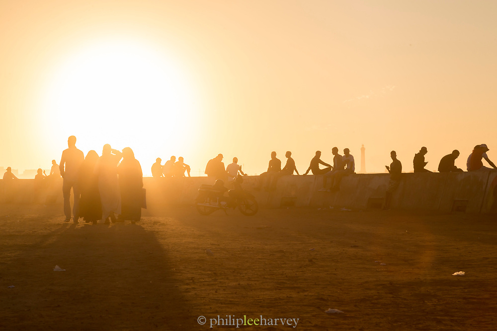 Silhouettes of tourists at corniche enjoying sea view at foggy sunset, Casablanca, Morocco