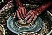 Hands of a potter forming clay on a potter's wheel