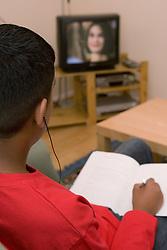 Boy doing his homework whilst watching TV,