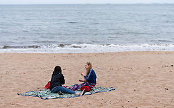 Portobello, Edinburgh, Scotland, UK. 5 April, 2020.  Images of Portobello promenade on the second Sunday of the coronavirus lockdown in the UK. Two young women have picnic on the beach.