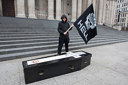 © licensed to London News Pictures. London, UK 22/05/2012. An Occupy London protester posing with a mock coffin prepared for Shell and a flag with Shell's logo drawn as a skull, outside St Paul's today (22/05/12). Photo credit: Tolga Akmen/LNP