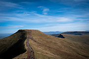 People walking across the summit of Corn Du twin topped with Pen y Fan and is the second highest peak in South Wales in the Brecon Beacons National Park, United Kingdom.  The rugged path connects the two mountain peaks.  The National Park was established in 1957 due to the spectacular landscape which is rich in natural beauty and is run by the National Trust.