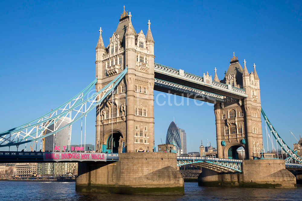 """The Bridges Not Walls movement drop a banner reading """"Bridges Not Walls' from Tower Bridge in London to coincide with banner drops all over the UK sending a clear message to Donald Trump the 45th president of the United States to build bridges not walls on the day of his inauguration."""