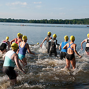 Female competitors in a local triathlon, Wakefield, Massachusetts enter Lake Quannapowitt for the swimming leg of the event