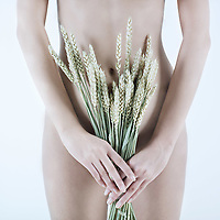 studio shot picture of a young beautiful breast naked caucasian woman holding grain