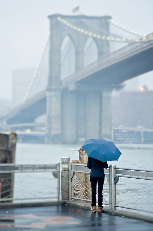 A girl with an umbrella watches the Brooklyn Bridge from Empire fulton Ferry Water Taxi Landing in Brooklyn, new York