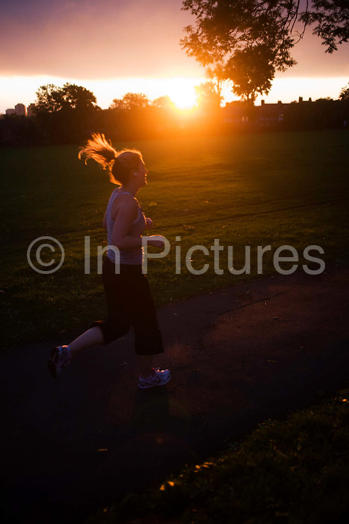 Setting sun with jogger in Ruskin Park in the borough of Lambeth, south London. Ruskin Park, Denmark Hill, SE24 (its post code) is a beautiful green space in this inner-city suburban district of Britain's capital, approximately 5 miles south from the River Thames. The jogger paces past the image as the sun sets against period homes of the Edwardian era, the age of innovative building in the new 20th Century. The properties overlook the borough park named after John Ruskin, the renowned artist and commentator who lived in nearby Herne Hill. It looks an affluent area, a prosperous location to invest in a mortgage in uncertain times with market prices falling during the credit crunch and recession.