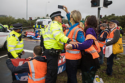 Colnbrook, UK. 27th September, 2021. Metropolitan Police officers monitor Insulate Britain climate activists who had previously blocked a M25 slip road at Junction 14 close to Heathrow airport as part of a campaign intended to push the UK government to make significant legislative change to start lowering emissions. The activists are demanding that the government immediately promises both to fully fund and ensure the insulation of all social housing in Britain by 2025 and to produce within four months a legally binding national plan to fully fund and ensure the full low-energy and low-carbon whole-house retrofit, with no externalised costs, of all homes in Britain by 2030.