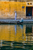 woman wearing a conical hat walking along Hoi An's picturesque waterfront lined with french colonial architecture.