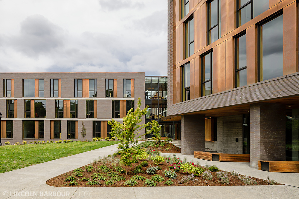 An exterior view of Trillium Residence Hall showing some of the elevation, copper panels, and landscaping.