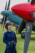 Elle Hooper a re-enactor in World War II WRAFuniform on the flight line with Spitfires and Hurricanes - The Duxford Battle of Britain Air Show is a finale to the centenary of the Royal Air Force (RAF) with a celebration of 100 years of RAF history and a vision of its innovative future capability.