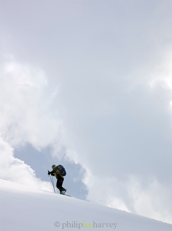 A hiker trekking in the snow by a volcanic steam vent in Daisetsuzan National Park, Hokkaid?, Japan