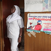 INDIVIDUAL(S) PHOTOGRAPHED: Somefun Olajide. LOCATION: Ikeja Primary Health Care Center, Lagos, Nigeria. CAPTION: The secretary of the Ikeja Primary Health Care Center updates the register that details beneficiaries' appointments, illnesses, treatments, and other health-related matters.