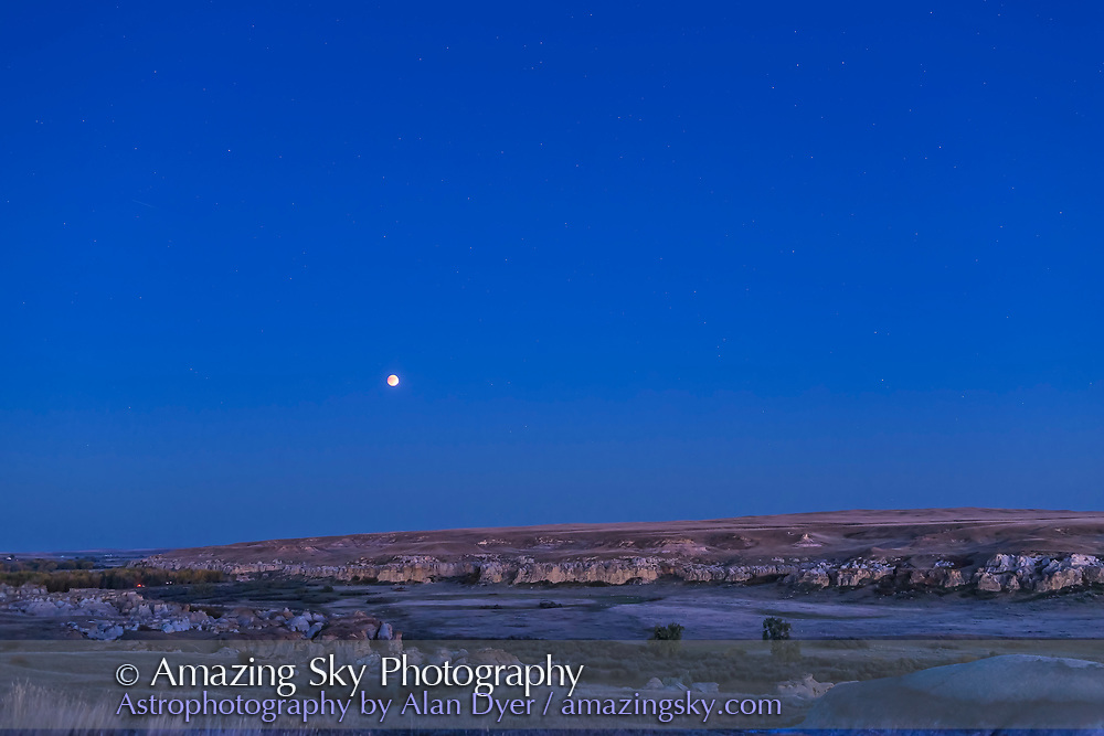 The Full Moon in total eclipse in the deep evening twilight over Writing-on-Stone Provincial Park, in southern Alberta, on September 27, 2015. This is a single exposure taken as part of a 730-frame time-lapse sequence. Exposure was 5 seconds at f/2.8 with the 35mm lens and Canon 6D at ISO 800.