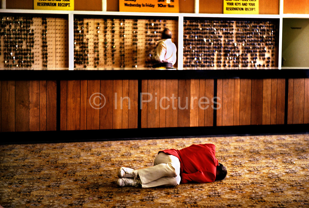 Redcoat asleep on the lobby floor of Butlins holiday camp, Skegness. The idea for the Red Coats came to Butlin early on in the Skegness Camps first season. He saw the first campers walking around looking bored and not making full use of the facilities. They had come to the camp looking for companionship and were not finding it. One of his assistants, Norman Bradford, started to jolly up proceedings by telling a few jokes to the campers assembled in the dining room. Butlin thought this was a good idea and the next day asked his colleague to go out and buy a distinctively coloured blazer - he did, in blue, primrose yellow and white, the camp colours. Butlin was not convinced and asked him instead to buy a red blazer. The Red Coats were then born. Butlins Skegness is a holiday camp located in Ingoldmells near Skegness in Lincolnshire. Sir William Butlin conceived of its creation based on his experiences at a Canadian summer camp in his youth and by observation of the actions of other holiday accommodation providers, both in seaside resort lodging houses and in earlier smaller holiday camps.