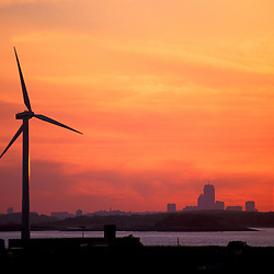 Wind Turbine in Hull, Massachusetts.  The Boston skyline is in the distance. Sunset.