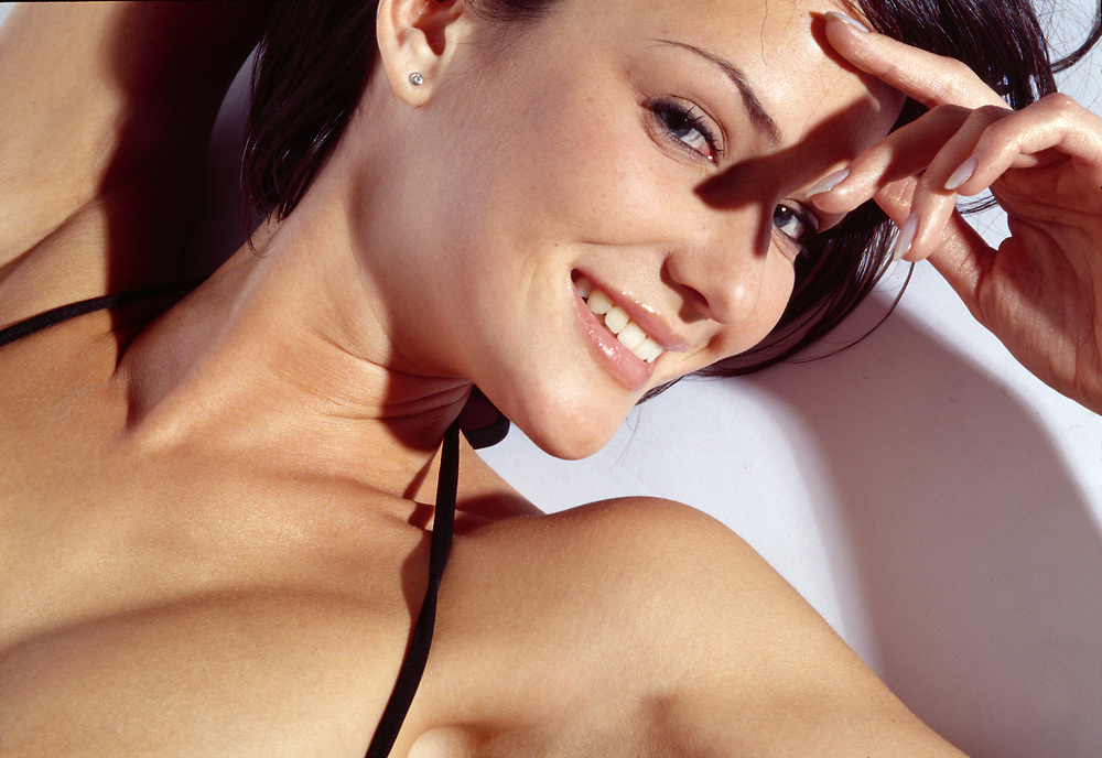 Close up of a happy woman laying down on a white background wearing a black bikini