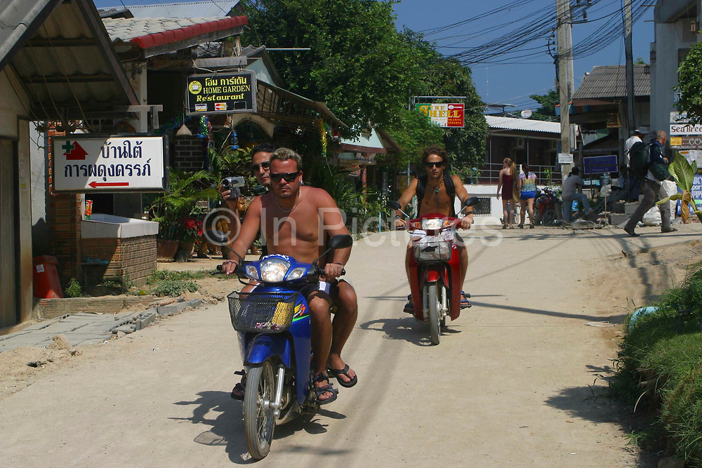 Westerners ride scooters through the streets of Hat Rin, Koh Phangnan, Thailand