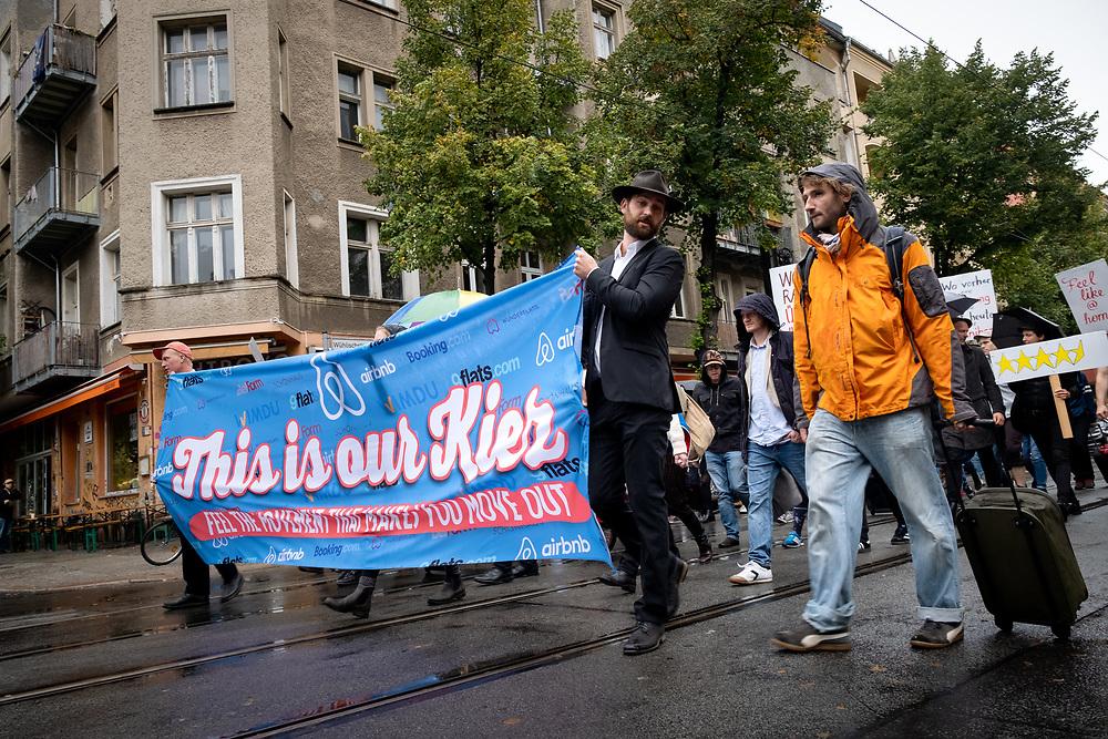 """Demonstration """"This is our Kiez"""" im Rahmen der Tumalwat  - Aktionstage: An die 50 Menschen protestieren in Berlin Friedrichshain mit einer satirischen Demonstration der Gruppe """"Friends of Airbnb"""" gegen Gentrifizierierung durch Investoren, gegen Zweckentfremdung von Wohnraum als Ferienwohnungen durch Ferienwohnungsanbieter wie Airbnb, 9flats, wimdu und booking.com und gegen teure Vermietung von möblierten Wohnungen auf Zeit durch Anbieter wie wunderflats, Belform oder Schönhaus.<br /> Demonstranten mit Banner: This is our Kiez. <br /> <br /> [© Christian Mang - Veroeffentlichung nur gg. Honorar (zzgl. MwSt.), Urhebervermerk und Beleg. Nur für redaktionelle Nutzung - Publication only with licence fee payment, copyright notice and voucher copy. For editorial use only - No model release. No property release. Kontakt: mail@christianmang.com.]"""