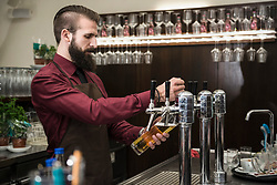 Young man filling glass of beer at restaurant