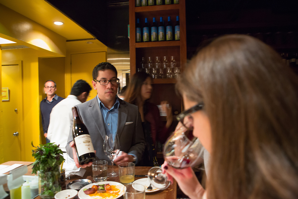 New York, NY, Sept. 28, 2013. Hector Perez, wine director of Casa Mono, at work during dinner. Perez showing diners the label of a bottle of Mugo Prado Enea Gran Reserva 2004.