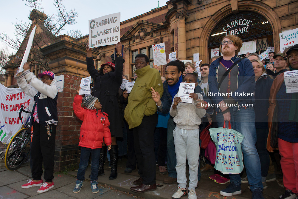 Local campaigners gather outside while protesting on the steps of Carnegie Library in Herne Hill, south London while occupiers remain inside the premises on day 5 of its occupation. The angry local community in the south London borough have occupied their important resource for learning and social hub for the weekend. After a long campaign by locals, Lambeth have gone ahead and closed the library's doors for the last time because they say, cuts to their budget mean millions must be saved.