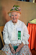 Old Bethpage, New York, USA. 28th September 2014. RUTH DEMARTINO is a volunteer wearing a traditional white blouse and flowered skirt and straw bonnet in the Exhibition Hall at the 172nd Long Island Fair, a six-day fall county fair held late September and early October. A yearly event since 1842, the old-time festival is now held at a reconstructed fairground at Old Bethpage Village Restoration.