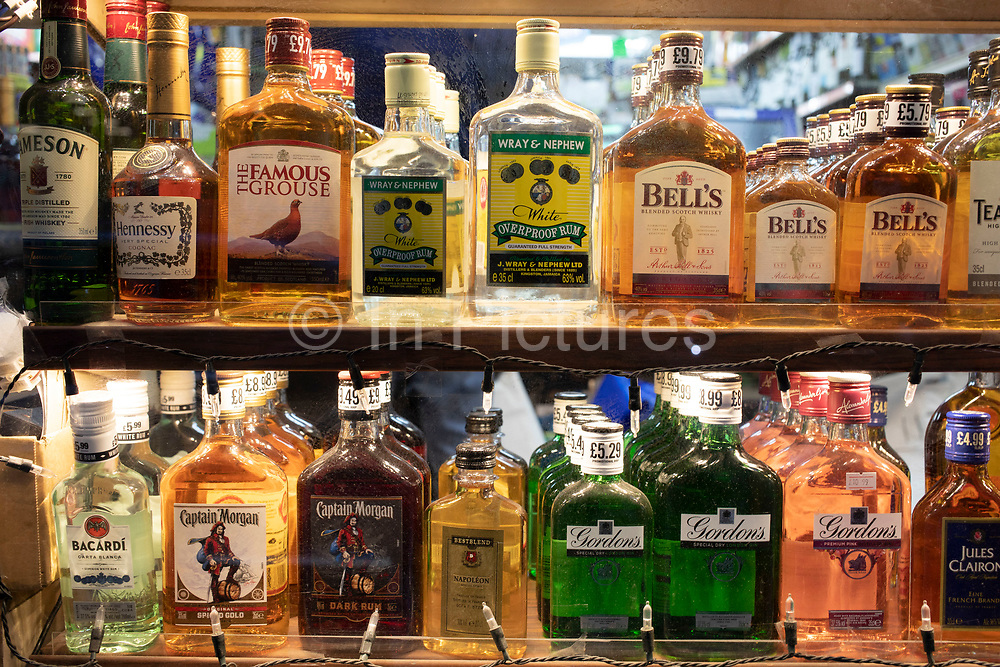 Small half and quarter bottles of spirits for sale in a corner shop window on 24th February 2020 in London, United Kingdom. Spirits are distilled alcohol in various forms, seen here as whiskey, rum and gin.