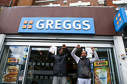 © Licensed to London News Pictures. 05/10/2021. London, UK. Men gesture to news of the possible price increase warning as they leaves a branch of Greggs in north London. Greggs, the bakery chain, warns of price increases of sausage rolls, pasties and steak bakes following the coronavirus and supply chain crises. Photo credit: Dinendra Haria/LNP