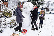 Family building a giant snow man outside their home in Moseley on 24th January 2021 in Birmingham, United Kingdom. Deep snow arrived in the Midlands giving some light relief and fun during the current lockdown for people who simply enjoyed the weather.