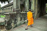Monk at Angkor Wat - built for the king Suryavarman II in the early 12th century.  Angkor is the only one to have remained a significant religious centre since its foundation.  First it was Hindu dedicated to the god Vishnu, then becoming Buddhist under other kings. The temple is admired for its grandeur and harmony  of architecture.