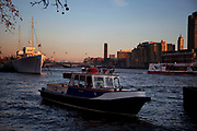 Boat on the River Thames comes in to it's mooring. In the evening light other ships and buildings are lit by warm light.